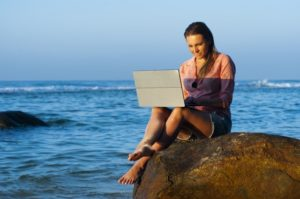 woman on laptop by the sea