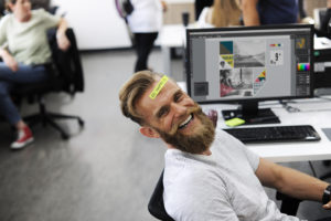 a man with a sticker on his head at a computer in an office